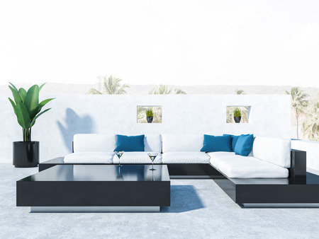Balcony of a luxury house with black and white sofas, blue cushions and black coffee table. Close up. Tropical view in background. 3d rendering
