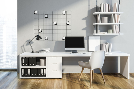 Interior of cozy home office with gray walls, wooden floor, neat table with computer on it and bookshelves. Small mock up photos on the wall. 3d rendering