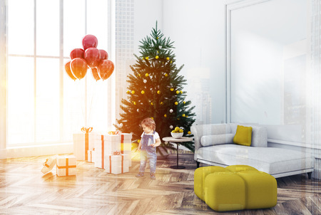 Cute little boy looking at presents in white wall living room corner with wooden floor and white sofa. Decorated Christmas tree with gifts and balloons in the corner. Toned image