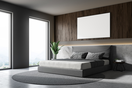 Side view of bedroom interior with gray and wooden walls, master bed standing on round carpet and concrete floor. Horizontal mock up poster on the wall. 3d rendering Banco de Imagens