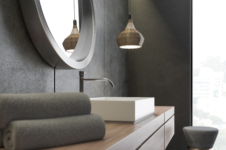Side view of white angular sink standing on wooden countertop with a round mirror hanging above it in cocnrete wall bathroom. 3d rendering Standard-Bild - 110562174