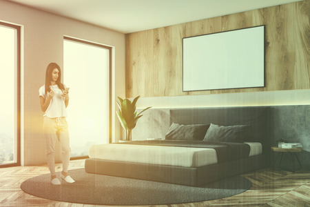 Woman with smartphone in bedroom with white and wooden walls, master bed standing on round carpet and wooden floor. Horizontal mock up poster on the wall. Toned image double exposure