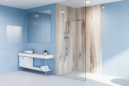 Corner of modern bathroom with blue walls, white floor, glass and wooden shower and white sink standing on white and wooden countertop with big square mirror hanging above it. 3d rendering