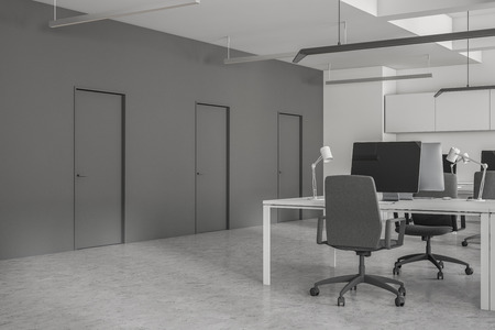 Close up of open space office with white walls, concrete floor, rows of computer tables with desktops on them. Row of doors in the wall. 3d rendering