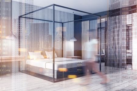 Woman walking in corner of modern bedroom with light wooden walls, wooden floor, white master bed and closet with mirror. Toned image double exposure blurred Stockfoto