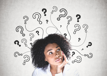 Pensive young African American woman wearing white shirt looking upwards sitting near concrete wall with many question marks drawn on it. Stockfoto