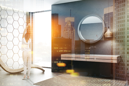 Woman in modern bathroom with black and gray honeycomb pattern walls and white double bathroom sink standing on wooden countertop. Round mirror and wooden armchair. Toned image double exposure Фото со стока