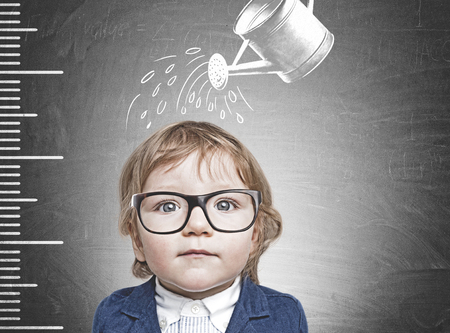 Adorable little boy wearing blue suit and glasses standing near blackboard with a ruler and watering can drawn above him. Concept of growth