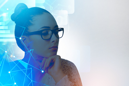 Pensive young businesswoman in glasses sitting on ver white background with immersive network interface and business stats. Toned image double exposure mock up
