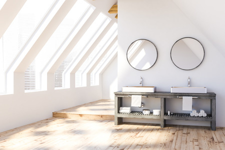 Attic bathroom interior with white walls, wooden floor and white double sink standing on gray countertop with round mirrors above it. 3d rendering Stok Fotoğraf