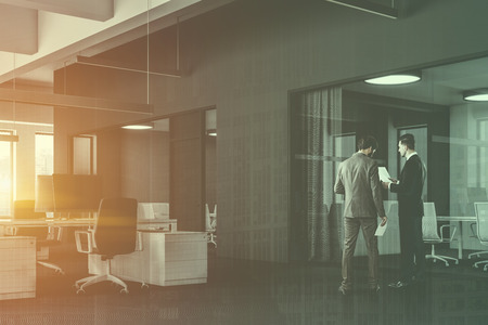 Businessmen in corner of open space office with gray and white walls, white computer tables and two meeting rooms with glass walls to the right. Toned image double exposure Standard-Bild - 112603913