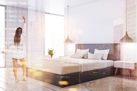 Woman in master bedroom corner with white walls, wooden floor, gray master bed with white covers, white bedside table and white sofa. Toned image double exposure Imagens