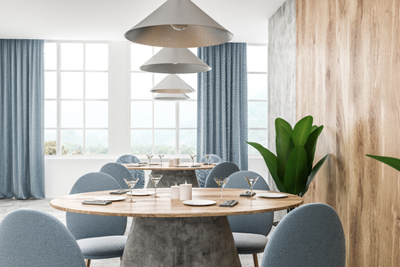 Modern cafe interior with white, wooden and concrete walls, concrete floor and round wooden table with blue chairs. Blue curtains on the windows. 3d rendering