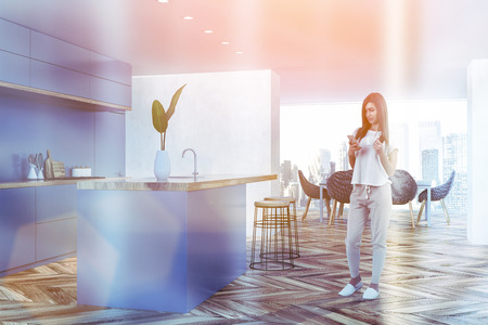 Woman in corner of modern kitchen and dining room with white walls, wooden floor, gray countertops, bar with round stools and dining table with chairs in the background. Toned image Reklamní fotografie