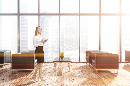 Woman in modern office waiting room with panoramic windows with a cityscape and wooden floor with black armchairs standing near coffee tables. Toned image