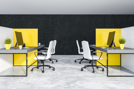 Interior of office with black walls and concrete floor and white and yellow cubicles with gray computer tables and white chairs. 3d rendering