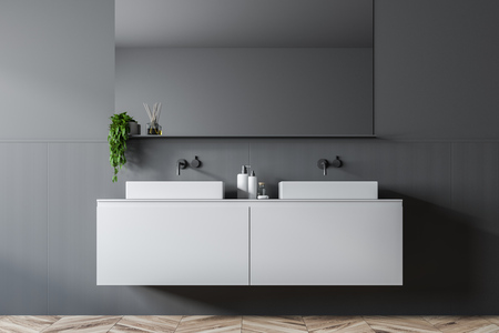 Double bathroom sink standing on white countertop in room with gray walls with a big horizontal mirror above it. 3d rendering Stock Photo