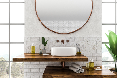 White round bathroom sink standing on wooden shelf with round mirror above it in room with white and brick walls and large windows. 3d rendering Stock Photo