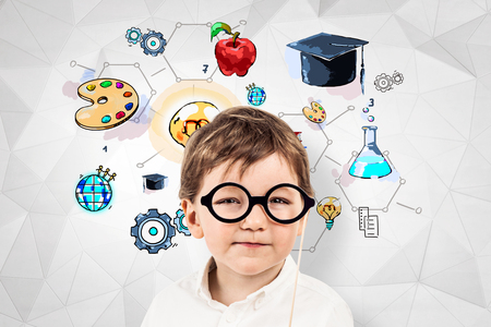 Thoughtful little boy in glasses and white shirt standing near geometric pattern wall with colorful education sketch. Stock Photo