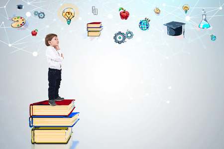 Side view of adorable little boy in white shirt and jeans thinking standing on stack of books near white wall with colorful education sketch. Mock up