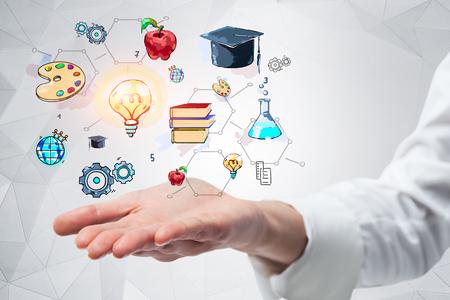 Hand van zakenman die wit overhemd draagt dat kleurrijke onderwijstekening houdt dichtbij witte muur met geometrisch patroon. Getinte afbeelding dubbele belichting