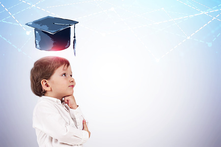 Side view of adorable little boy in white shirt thinking standing near white wall with graduation hat and graphs drawn above his head. Mock up