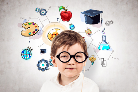 Thoughtful little boy in glasses and white shirt standing near concrete wall with colorful education sketch. Stock Photo