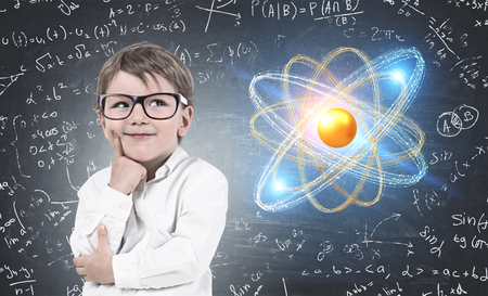 Portrait of adorable little boy with fair hair wearing glasses and white shirt standing near blackboard with formulas and atom model and thinking 写真素材