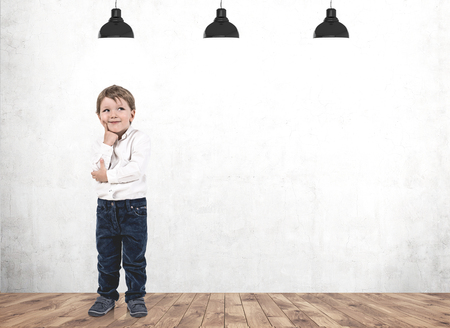 Portrait of adorable little boy with fair hair wearing blue jeans and white shirt standing near concrete wall and thinking. Mock up