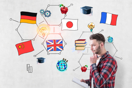 Pensive young man wearing checkered shirt and holding copybook standing near concrete wall with colorful international education sketch