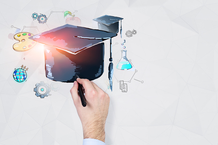 Hand of businessman wearing white shirt drawing colorful education sketch and graduation hat on white wall with geometric pattern. Mock up toned image
