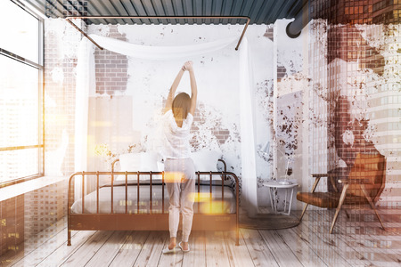 Woman in grunge bedroom interior with brick walls, wooden floor, copper master bed with gray cover and beige leather armchair. Toned image double exposure