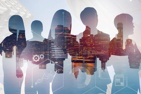 Silhouetten von Geschäftsleuten über Nachtstadtbildhintergrund mit Doppelbelichtung von Geschäftsinfografiken. Getöntes Bild Standard-Bild