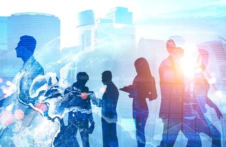 Silhouettes de gens d'affaires travaillant ensemble sur fond de paysage urbain moderne avec hologramme de la Terre. Commerce international. Banque d'images
