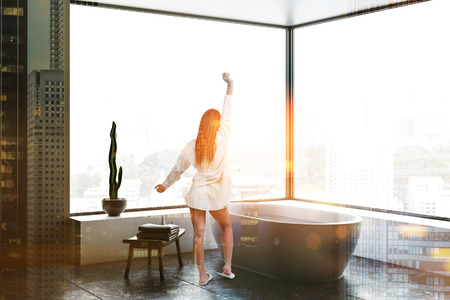 Woman in corner of panoramic bathroom with gray walls, tiled floor, white bathtub standing near wooden chair and white drawers. Toned image double exposure 스톡 콘텐츠