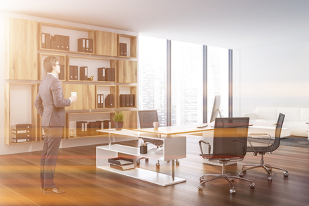 Businessman in interior of ceo office with white walls, dark wooden floor, white and wooden computer table and wooden shelves with folders. White sofa near coffee table. Toned image Stock Photo