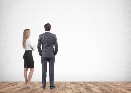 Full length portrait of blonde businesswoman and dark haired businessman in suit standing in empty room looking at blank wall. Mock up 免版税图像