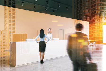 Business people near white reception desk standing in modern office with orange walls, concrete floor, two doors and a leather sofa. Toned image double exposure