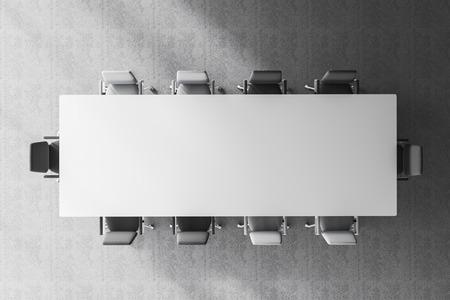 Vista superior de la mesa de la sala de reuniones blanca con sillas grises y blancas a su alrededor en la habitación con piso de concreto. Representación 3d Foto de archivo