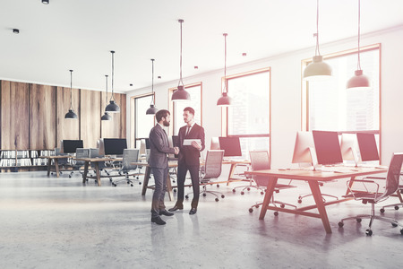 Businessmen in interior of open space office with white and light wooden walls, loft windows, concrete floor and rows of light wooden computer tables. Toned image