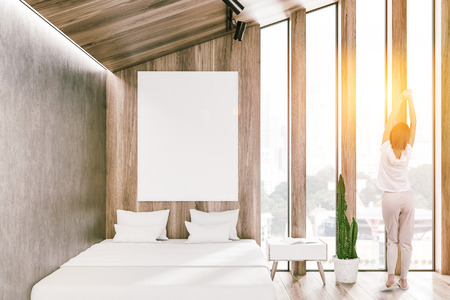 Woman in interior of attic bedroom with light wooden and concrete walls, wooden floor, white master bed with vertical poster above it and bedside table. Toned image mock up Banque d'images - 115173548