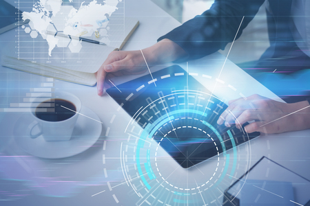Hands of businesswoman working with tablet in office with double exposure of hud and business infographics interface. Stock Photo