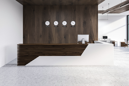 White and wooden reception desk with computer on it and clocks showing world time with office in the background. 3d rendering Banque d'images - 115174146