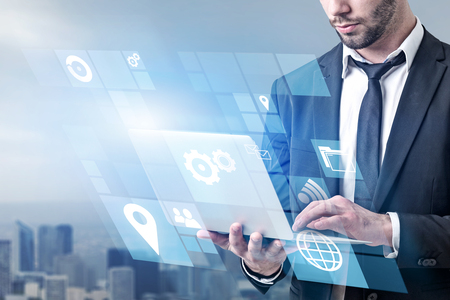 Unrecognizable businessman holding laptop with business interface icons standing over blurred cityscape background. Toned image double exposure