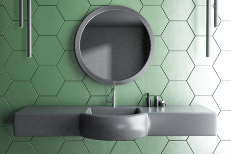 Original gray sink with round mirror above it standing in modern bathroom interior with green honeycomb pattern walls. 3d rendering