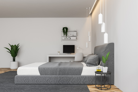 Side view of modern bedroom with white walls, wooden floor, gray master bed on carpet and white computer table. 3d rendering Stock Photo