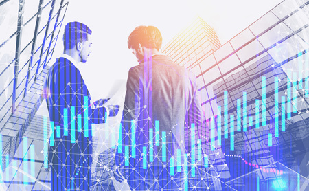 Rear view of two young businessmen with documents discussing work in city with double exposure of graphs. Stock market concept. Toned image