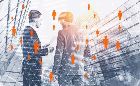 Rear view of two businessmen discussing document over skyscraper background with double exposure of global people network hologram. Toned image.