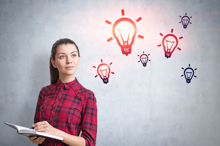 Young woman in checkered shirt holding copybook and pen standing near concrete wall with light bulbs drawn on it. Concept of idea Stockfoto