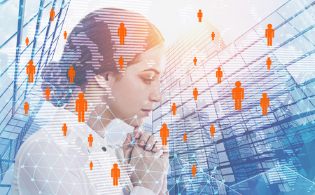 Side view of pensive businesswoman with dark hair over skyscraper background with double exposure of global people network hologram. Toned image.